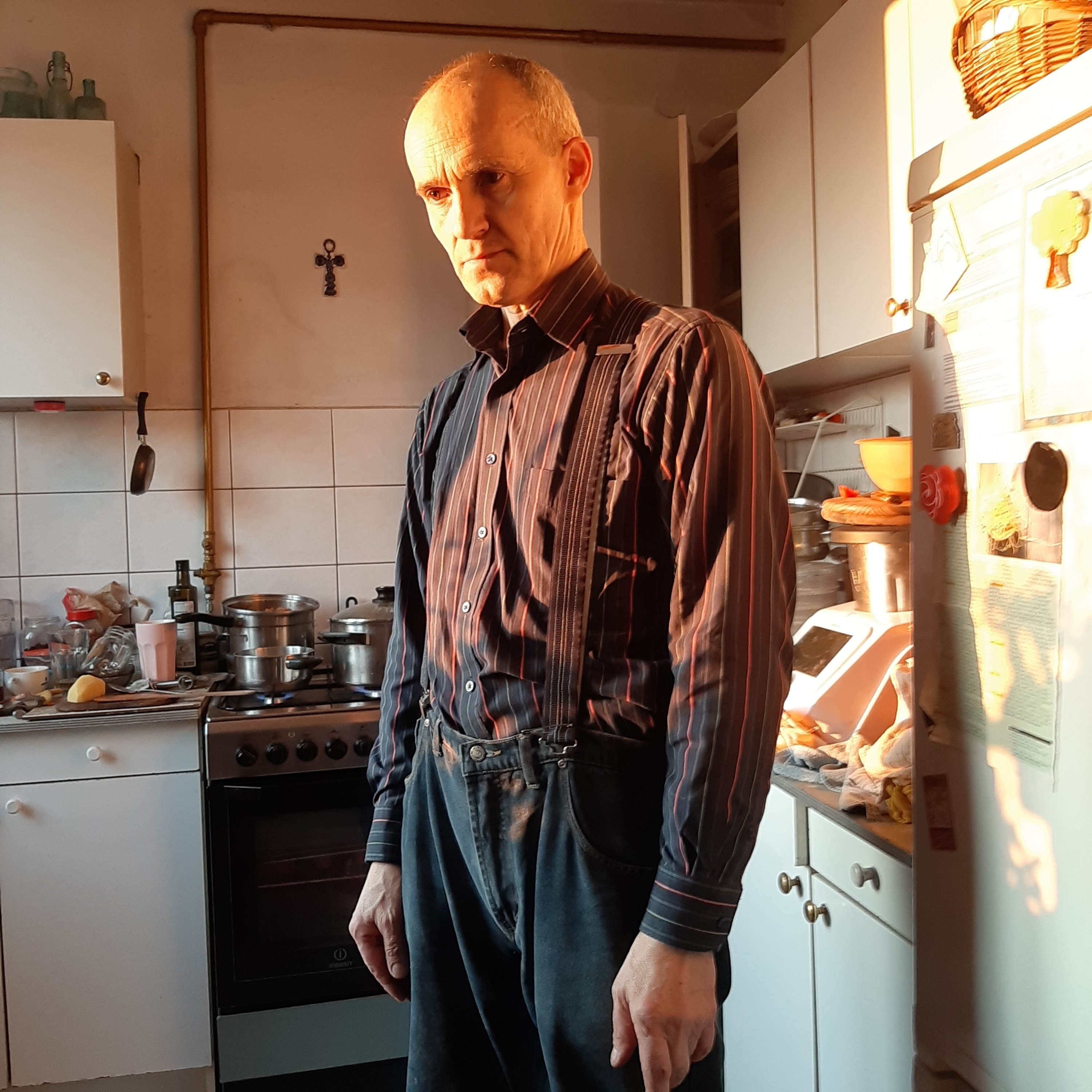 A man in overalls and a striped shirt stands in a kitchen