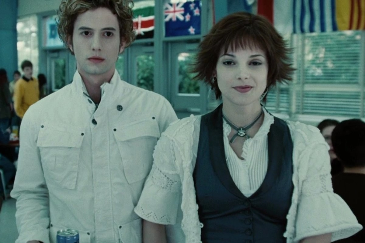 Ashley Greene as Alice smiles coyly while holding hands with boyfriend Jasper (Jackson Rathbone).
