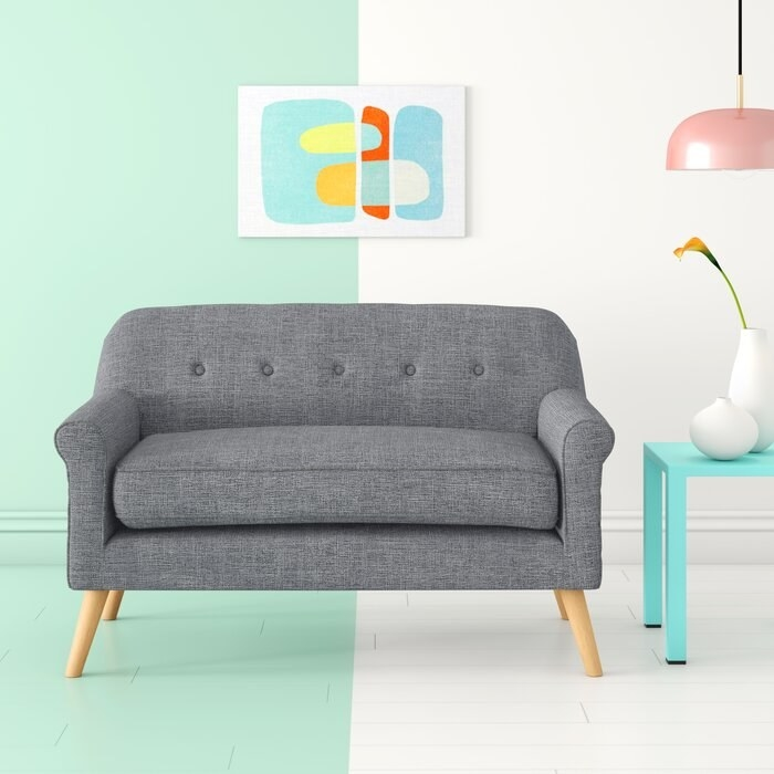 Flared arm loveseat in gray fabric with mid-century wooden legs