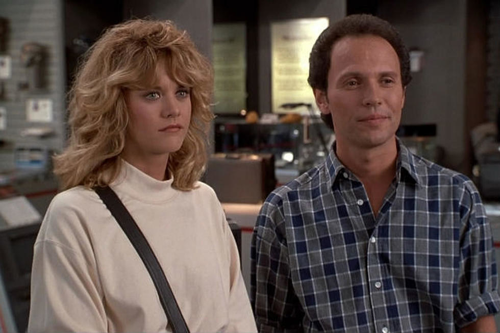 Meg Ryan as Sally and Billy Crystal as Harry stand next to each other in an office.