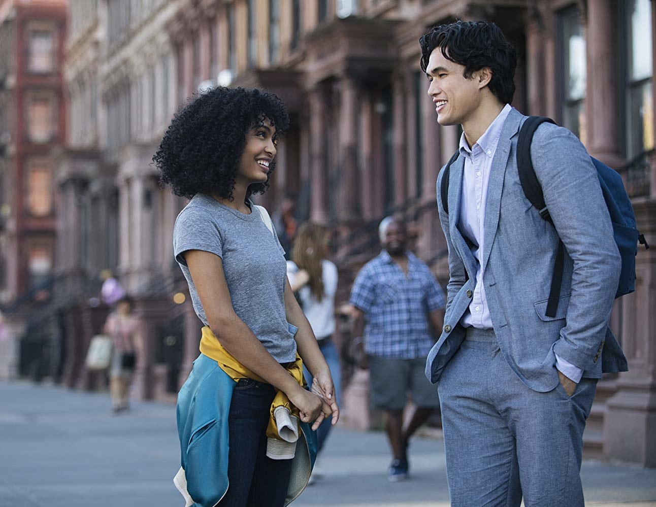 Yara Shahidi as Natasha smiles and talks with Daniel (Charles Melton) in the streets of New York City.