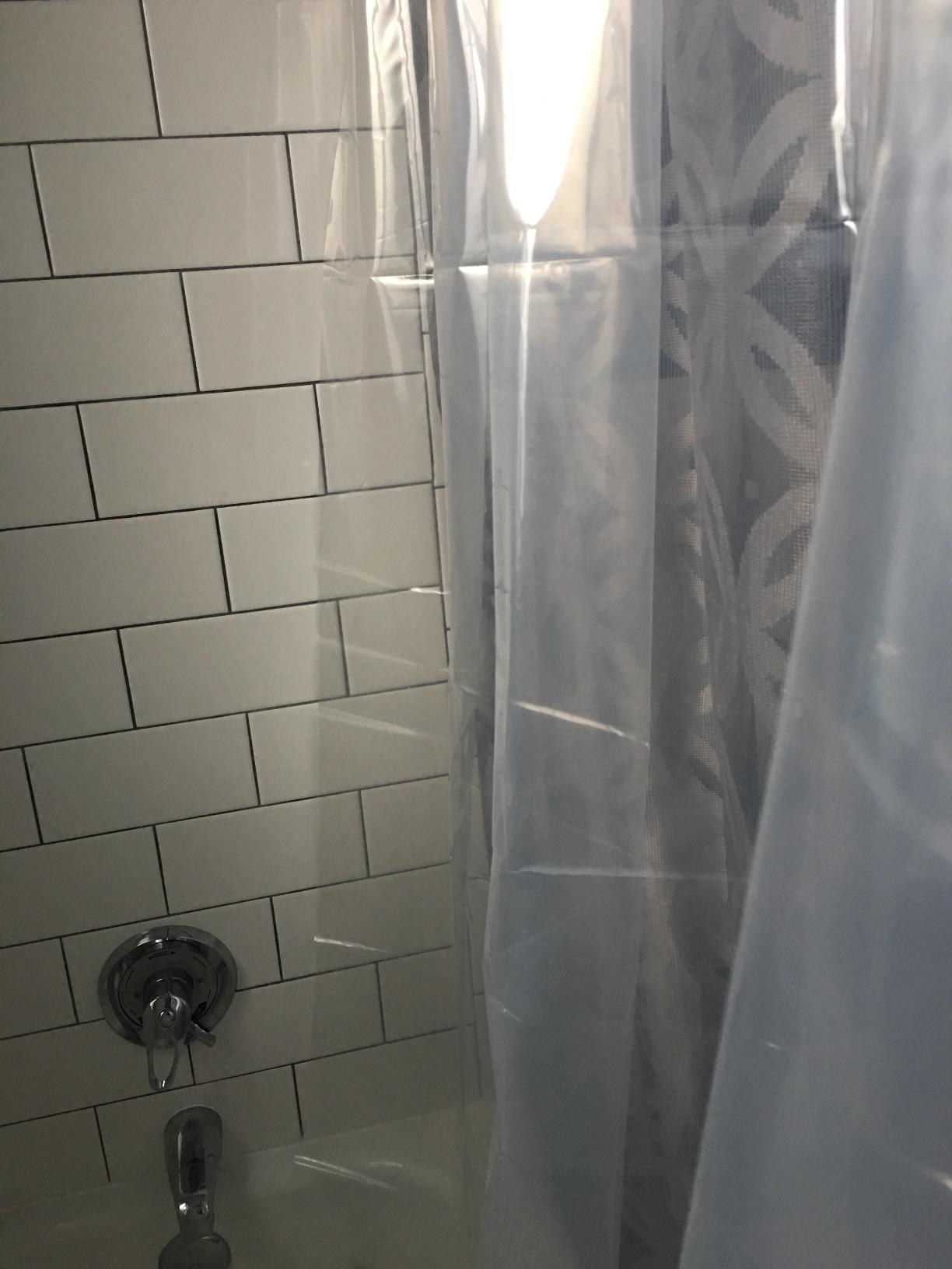 A reviewer's photo of a clear shower curtain in the bathroom