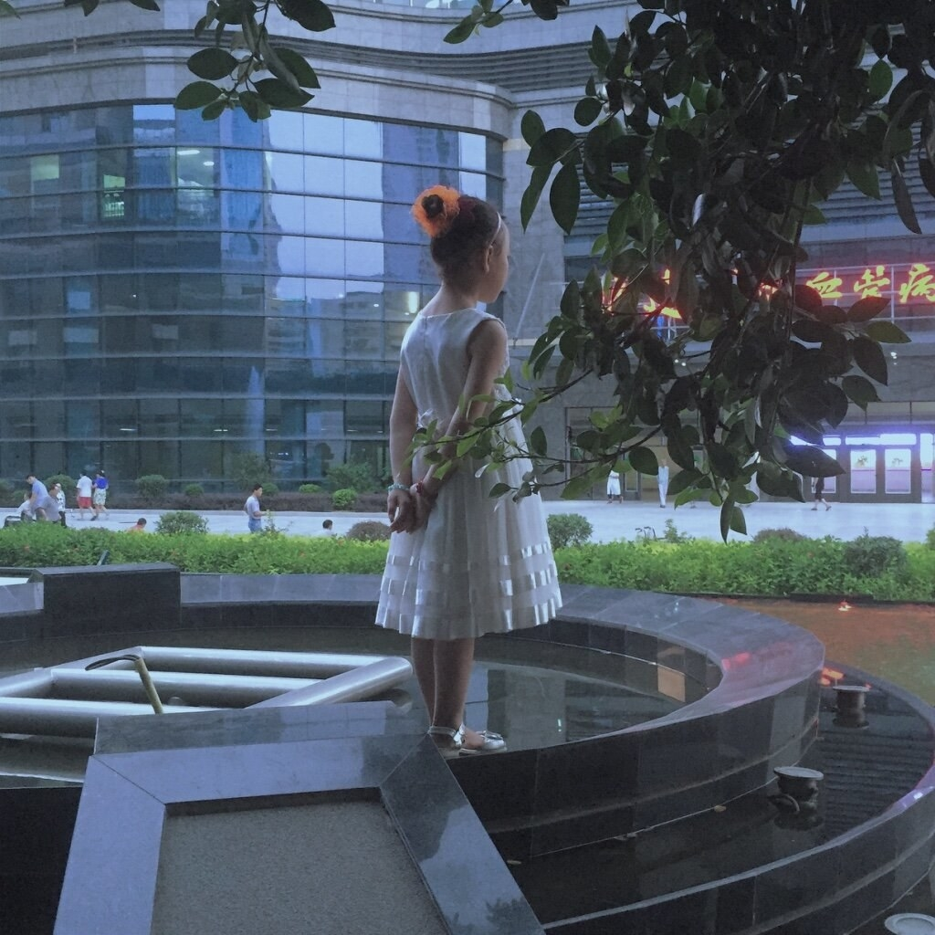 A girl in a white dress looks out at the street