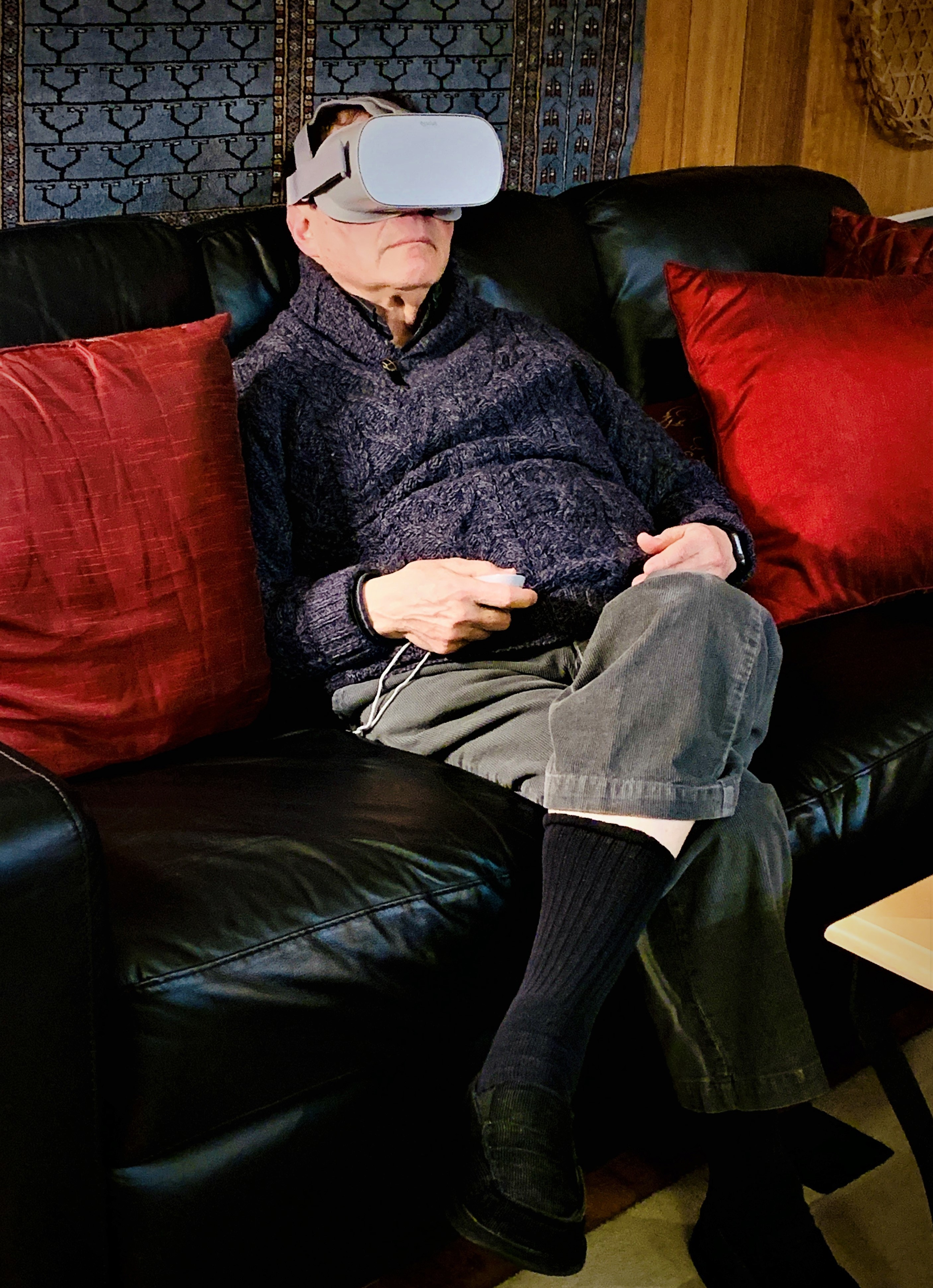An older man wearing VR glasses sits on a couch