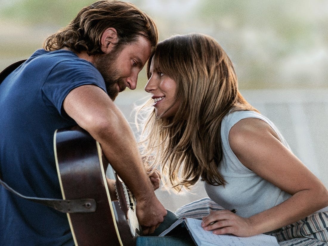 Lady Gaga as Ally leans in to kiss Jack (Bradley Cooper) while he plays the guitar.