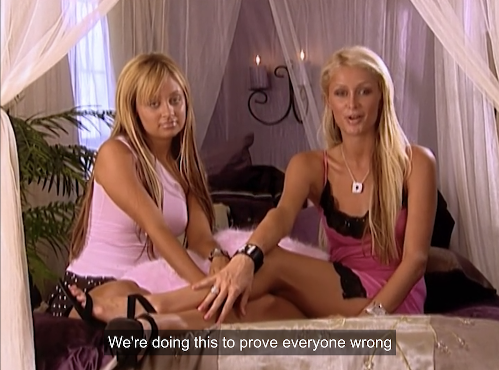 Nicole and Paris laying on a fancy bed and saying they're going to prove their haters wrong.