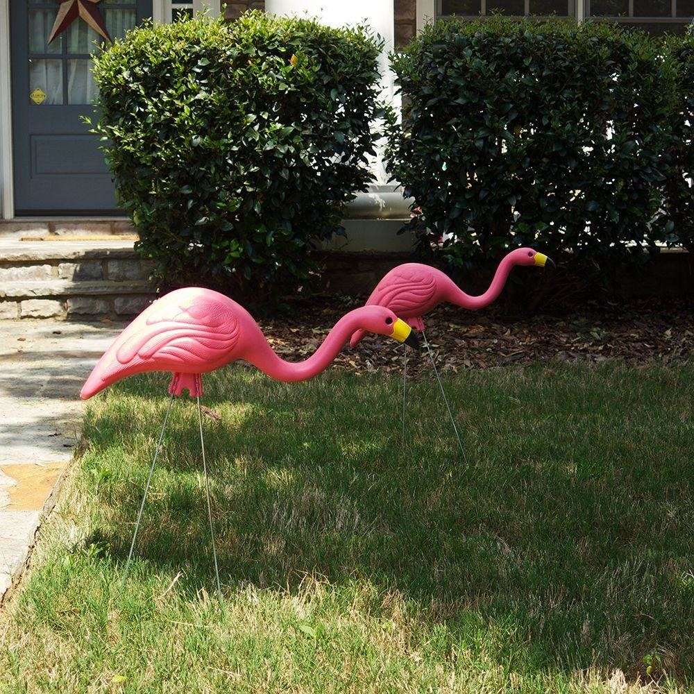 two pink plastic flamingo lawn ornaments