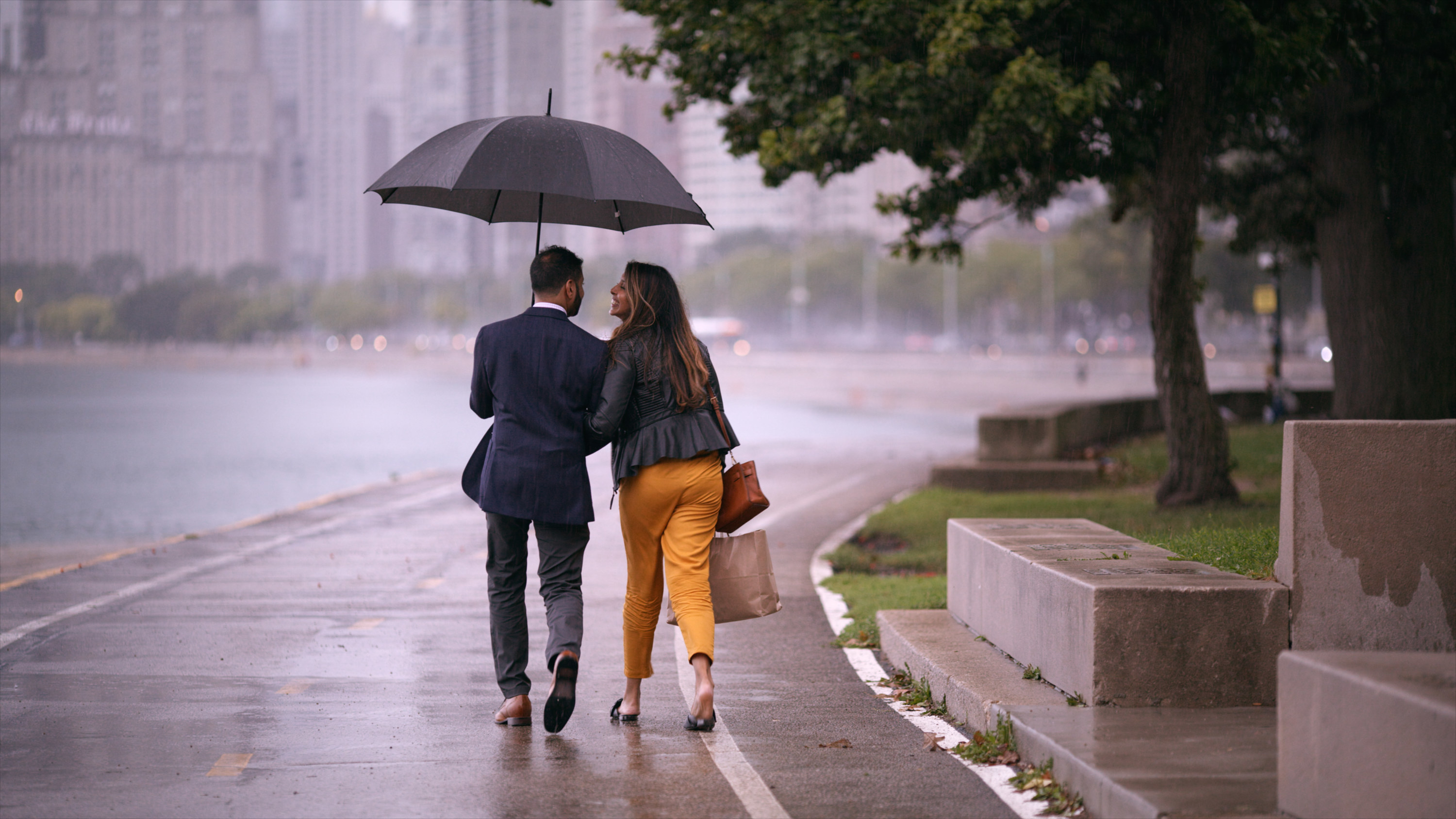 Nadia and Shekar walking in the rain on a date