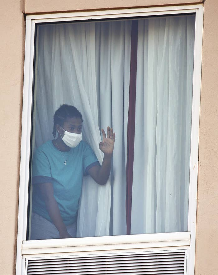 A girl wearing a face mask waves from a hotel room window