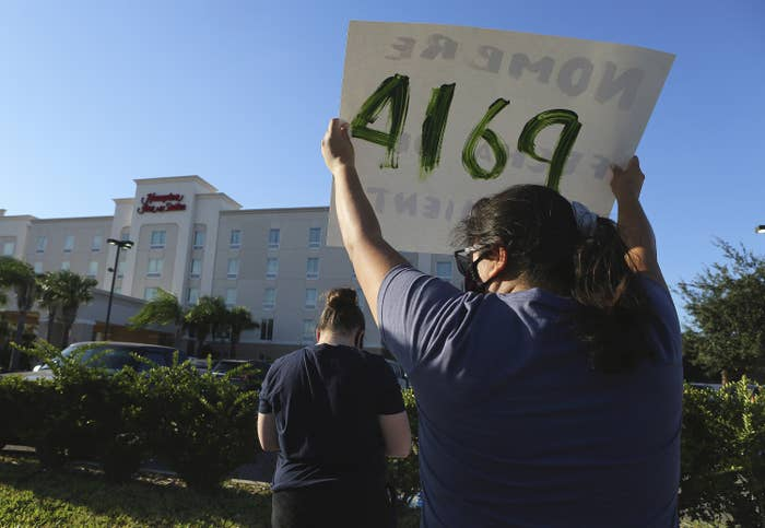A person with their back to the camera holds up a protest sign, facing a Hampton Inn hotel