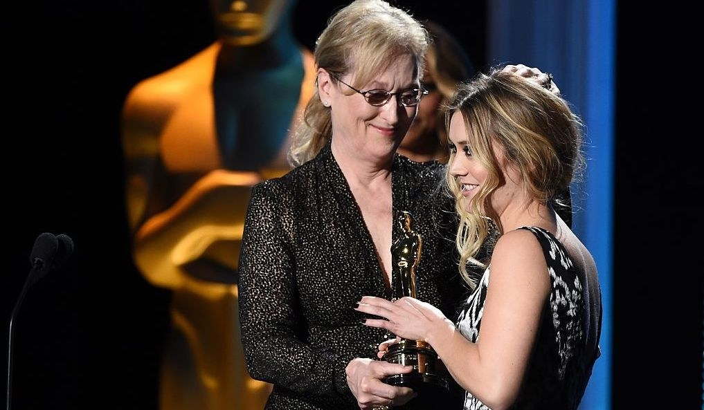 A Getty image showing Meryl Streep and Billie Lourd both holding and award and embracing on stage at an event