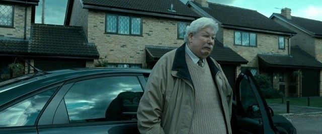 Mr. Dursley standing outside of his house, sad and solum, ready to drive away with his family
