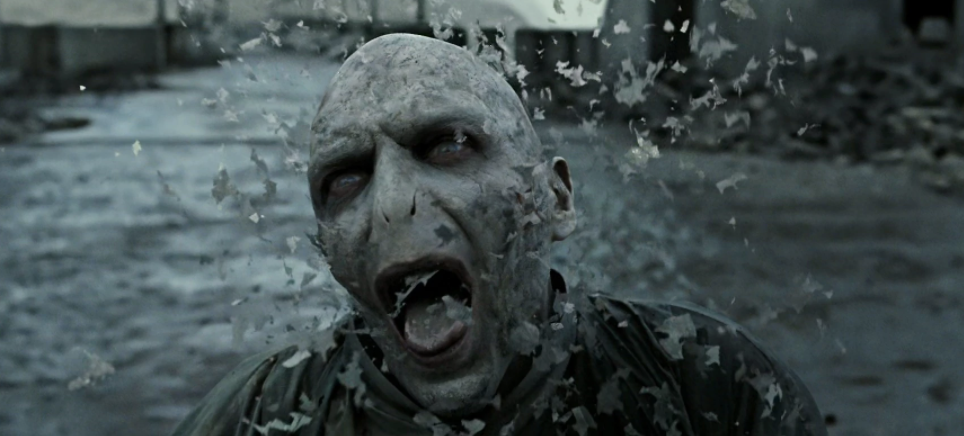 Voldemort dying towards the end of The Battle of Hogwarts, his body disintegrating, with a painful expression on his face