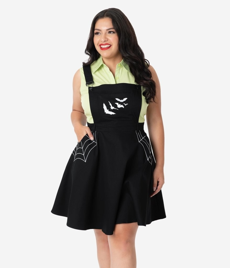 plus-size model wearing black pinafore dress with white spiderweb design at pockets and bats on the chest