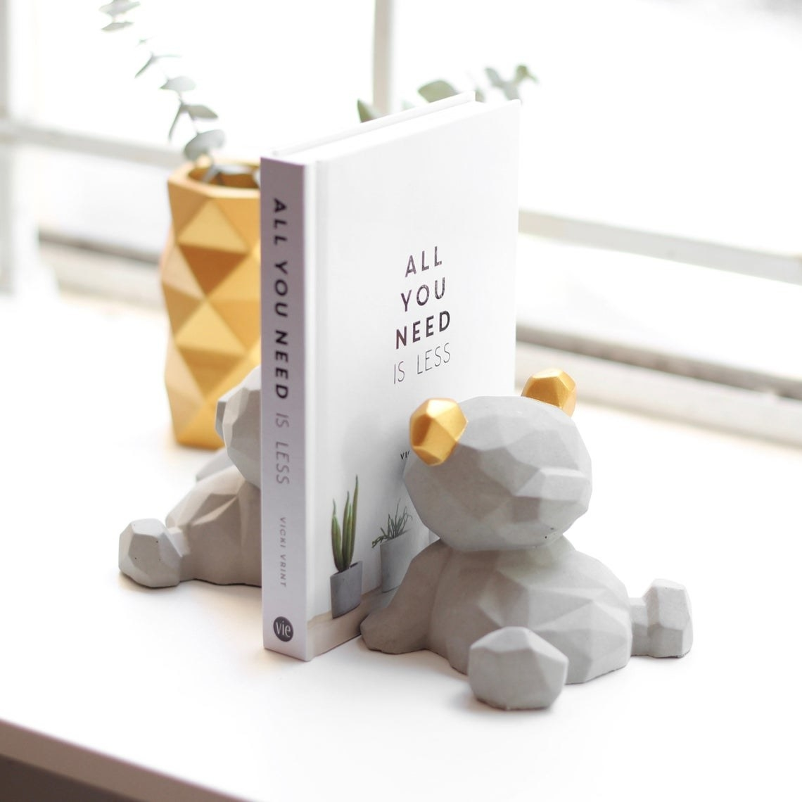 A pair of clay bookends in the shape of small bears with a book between them