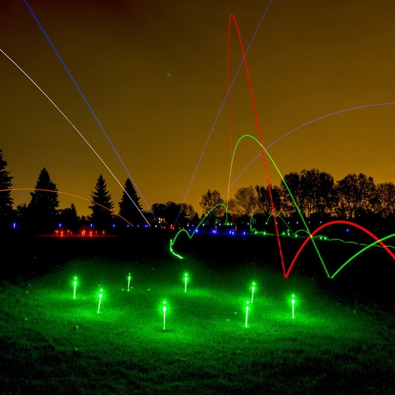 an array of light up stakes and light up golf balls in a yard
