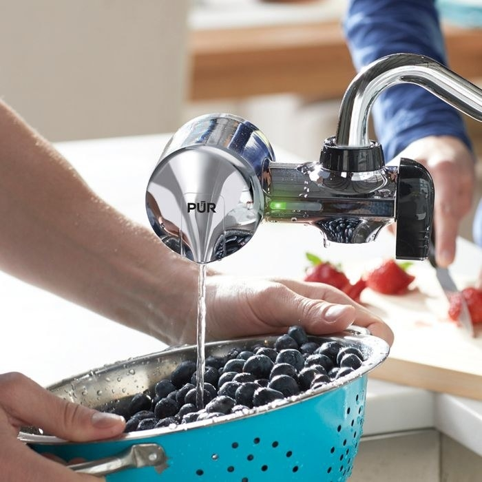 A model washes blueberries under water running through the PUR Advanced Faucet Filtration System
