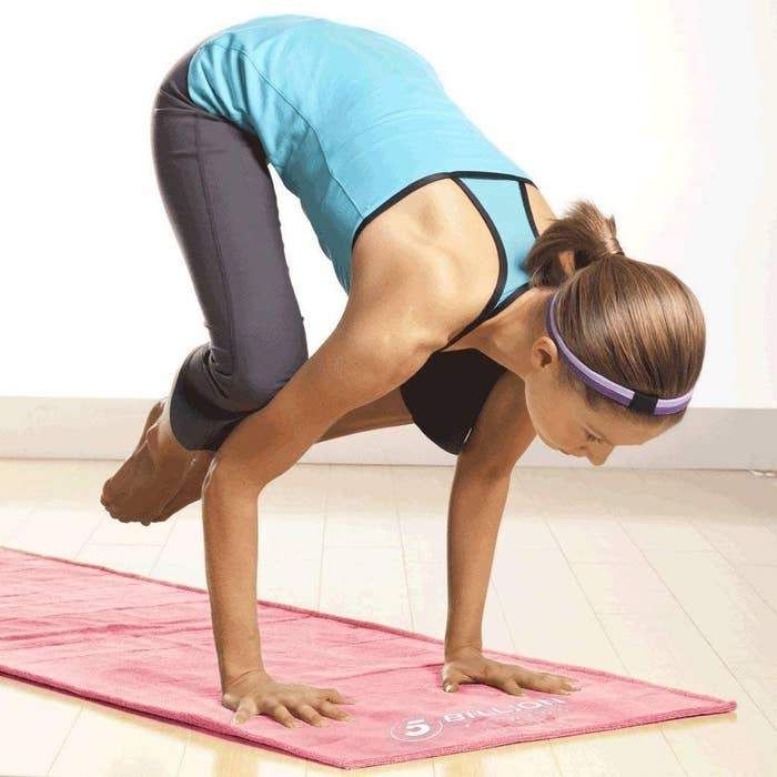 A person is doing crow pose on the mat in an empty studio