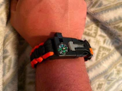 Reviewer wears orange and black paracord on their wrist