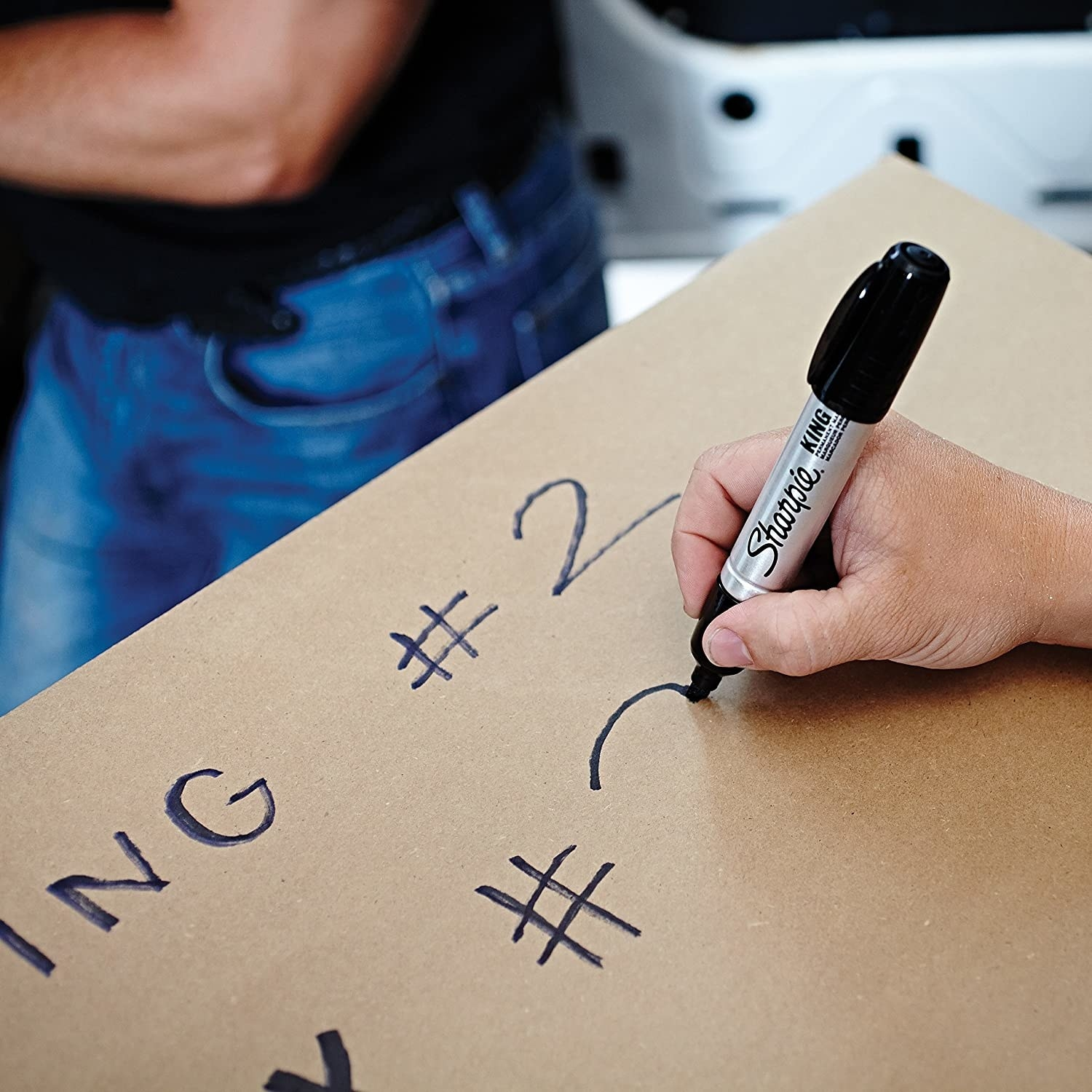 A model's hand holding a large black ink Sharpie marker writing on a cardboard box