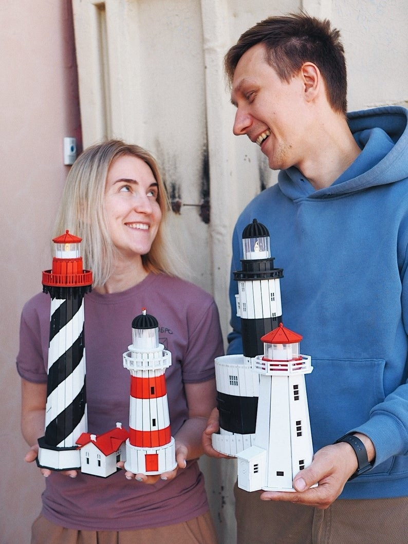 Two people holding completed lighthouses, which are about the same size as their torsos