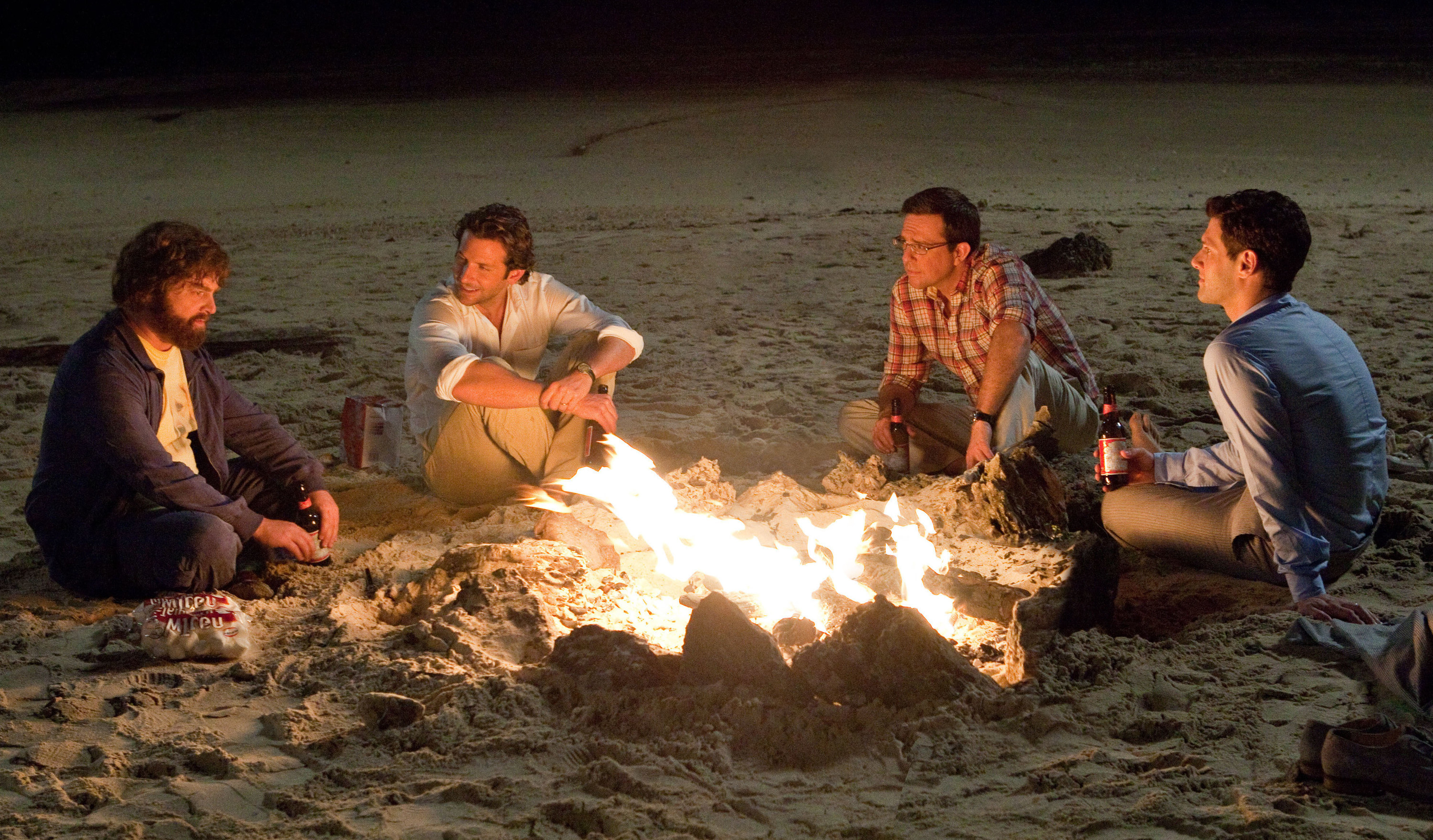 A still from the movie The Hangover shows the four guys on the beach sitting around a small bonfire