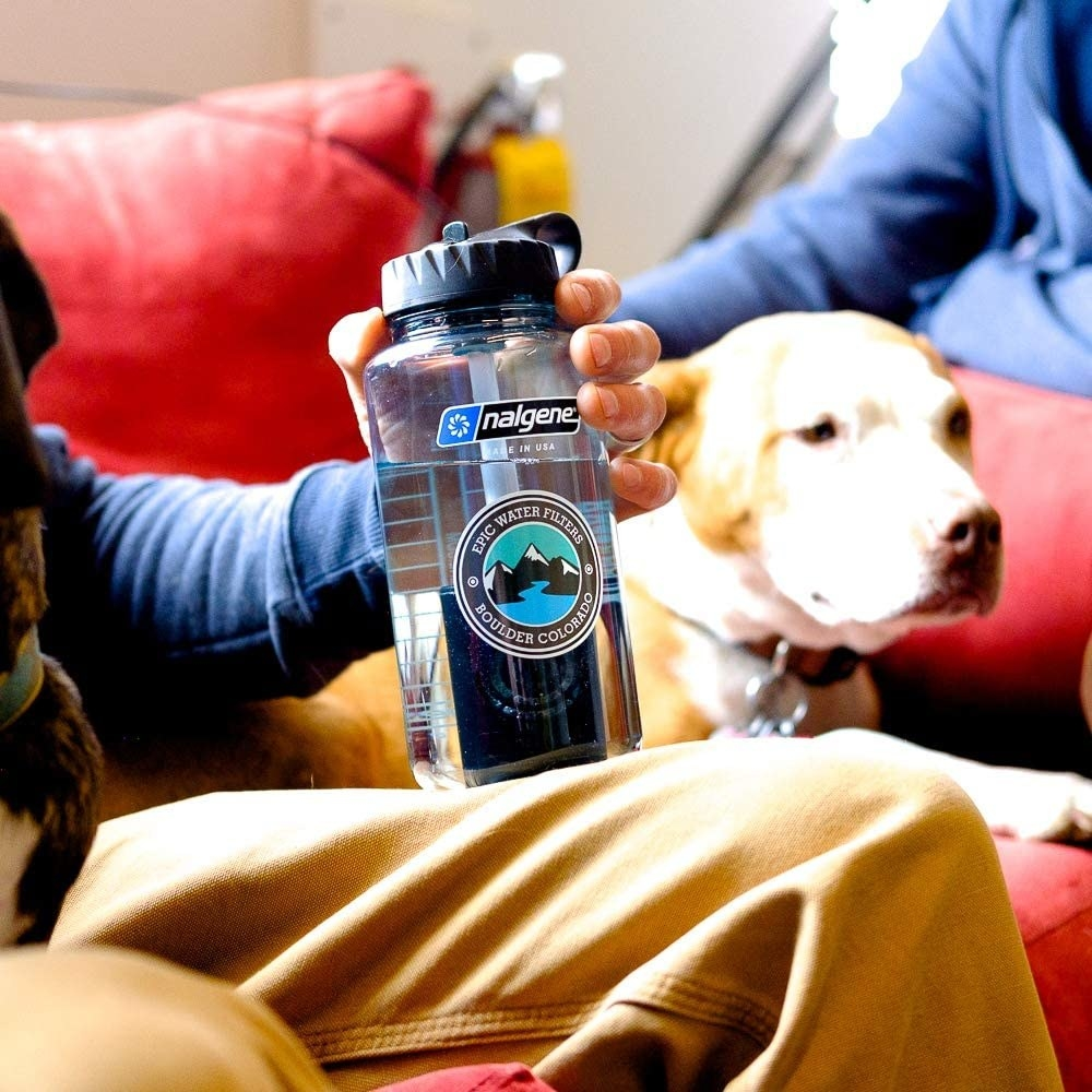 A person resting their water-filtering Nalgene bottle on their knee