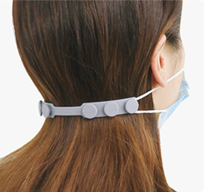 A model wearing a mask that is pulled together around the back of their head by the silicone ear saver, which has three different toggles on the back for sizing