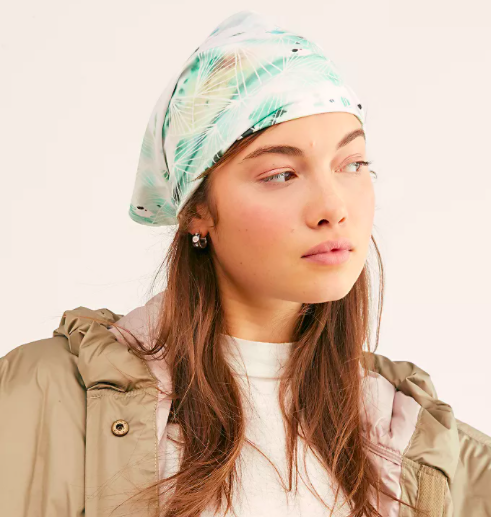 A person wearing the wrap as a head scarf while looking off camera