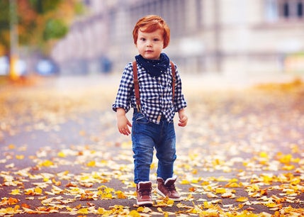 Little boy in plaid shirt, scarf, jeans, and boots