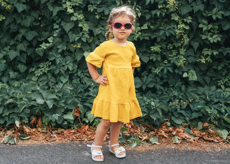 Little girl in a dress and sunglasses