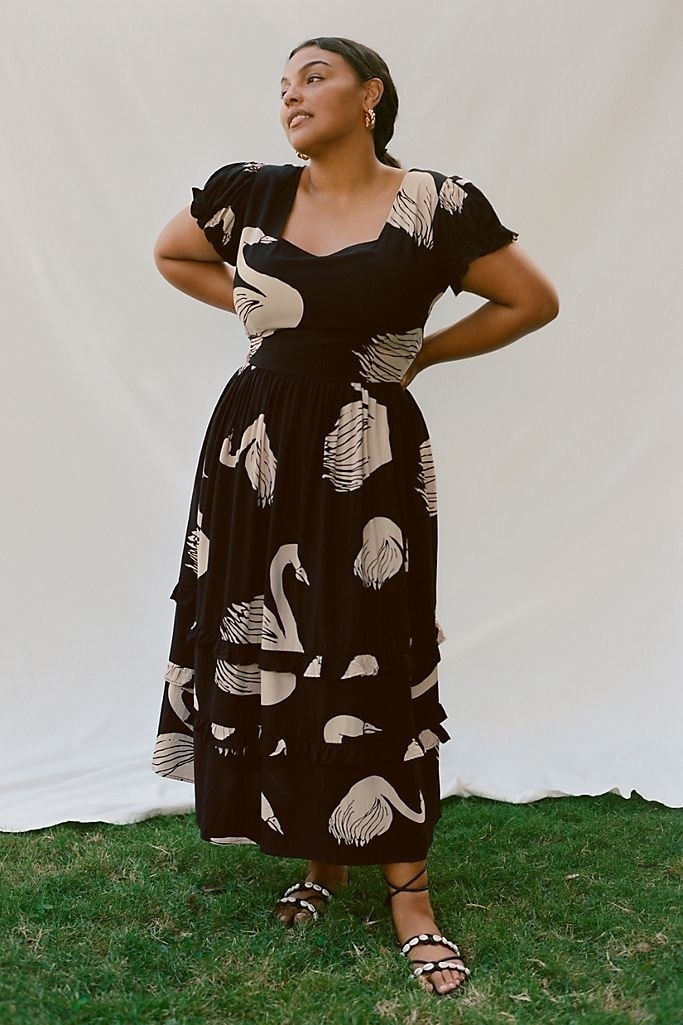 A model wearing the dress with strappy sandals. The dress has a sweetheart neckline, short sleeves, a fitted waist, and ruffles on the bottom.