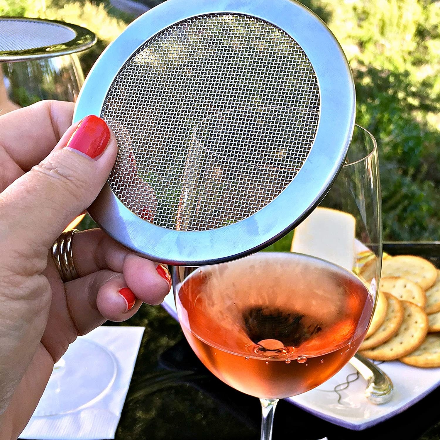 A person holding the mesh filer above their wine glass
