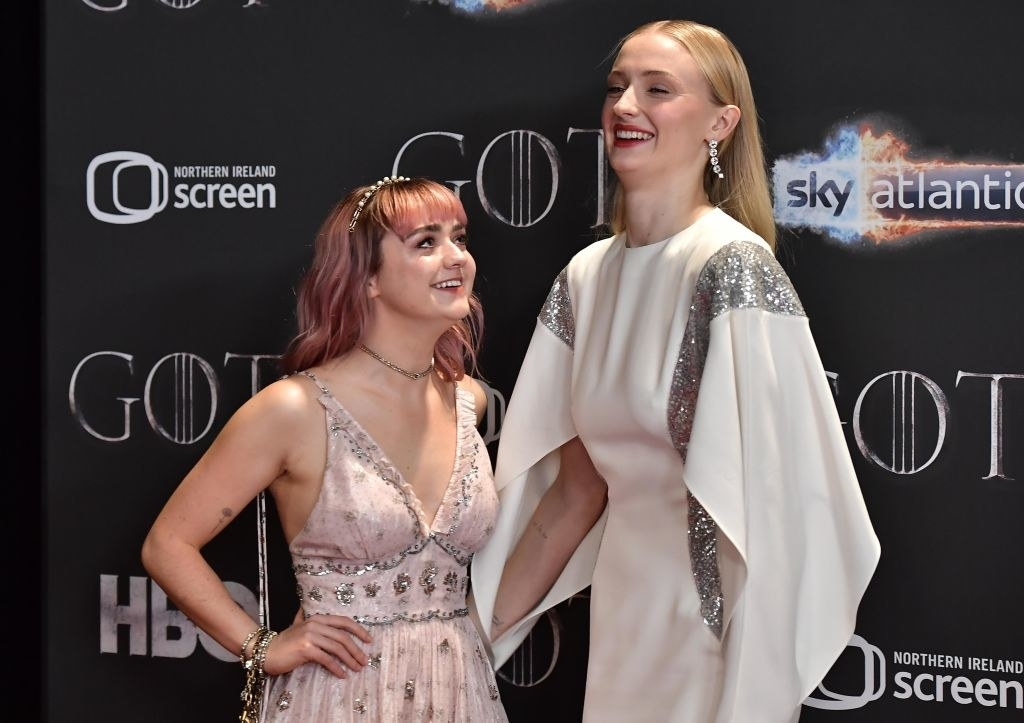 Maisie Williams and Sophie Turner smiling on the red carpet together.
