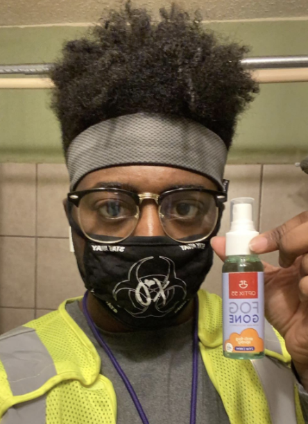 A reviewer image of a person wearing unfogged glasses with their face mask holding up the spray