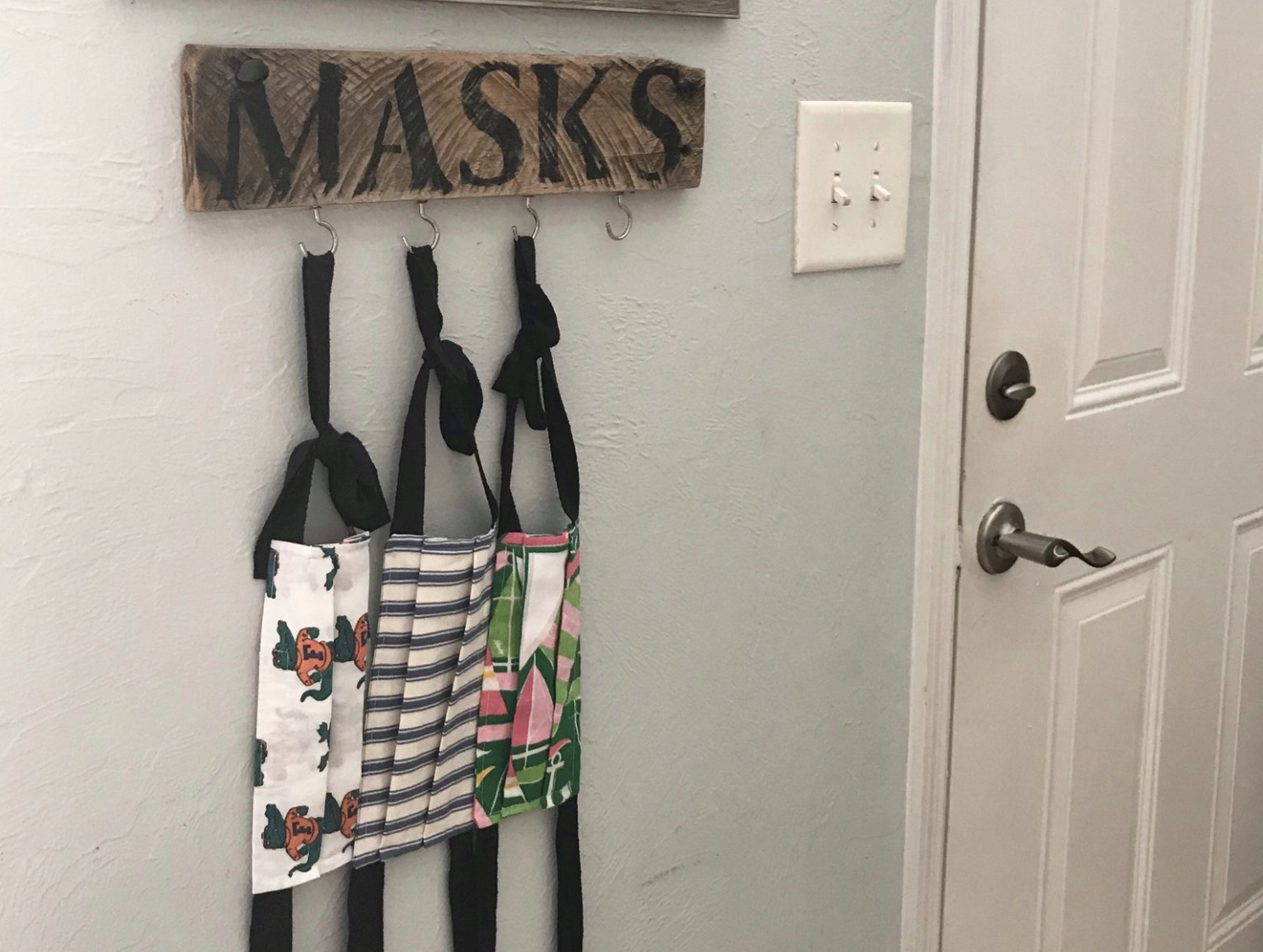 "A wooden post that says ""masks"" in black and has four hooks for masks to hang from"