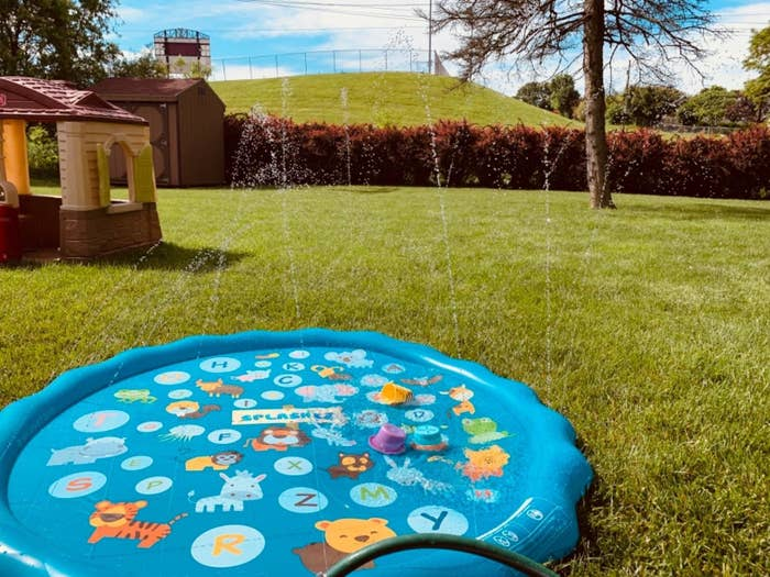 A blue circular splash pad with colorful animals and letters spraying water all around