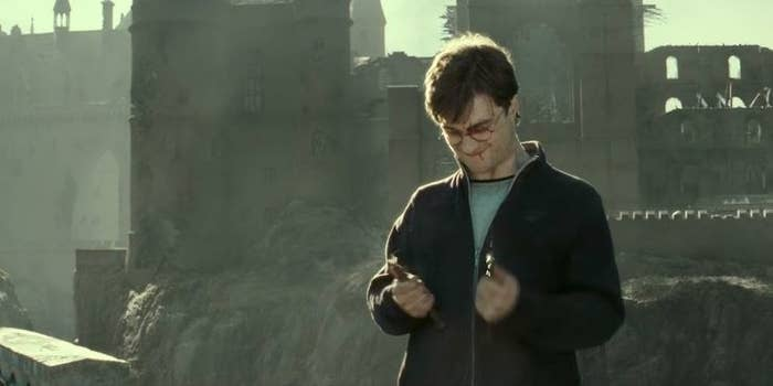 Harry breaking the Elder Wand with delight after the Battle of Hogwarts, standing in front of a destroyed school