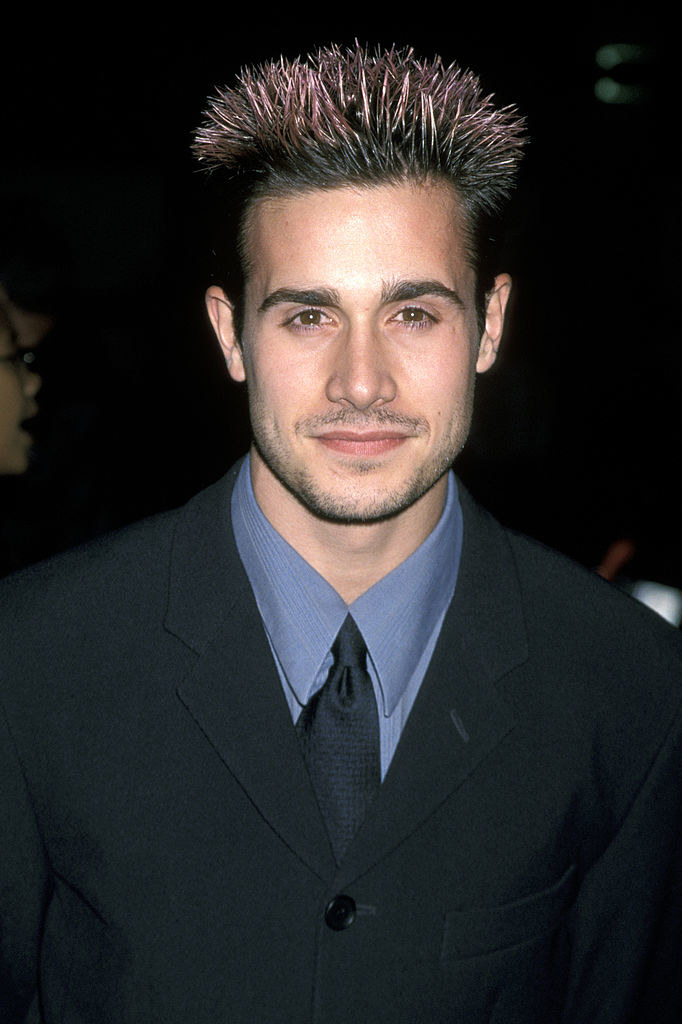 A photo of Freddie Prinze Jr. in a suit with spiky frosted tip hair.