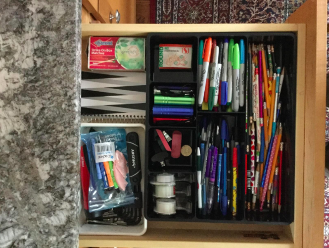 The desk drawer organizer in a customer's drawer, full of markers, pens, and miscellaneous items