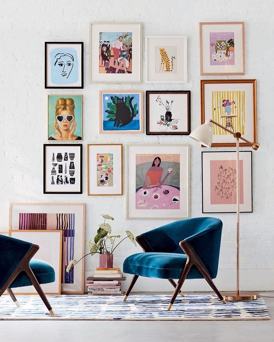 A simple gallery wall extends from the floor to ceiling behind two armchairs and a lamp