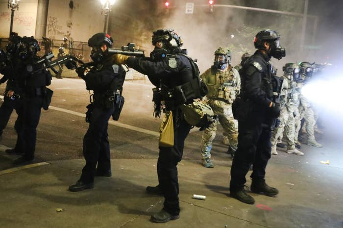 Federal officers dressed in all black with helmets and gas masks aim their weapons