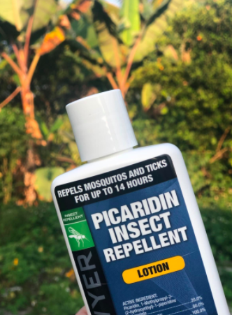 Reviewer holds bottle of Picaridin Insect Repellent in their hands while enjoying time outside
