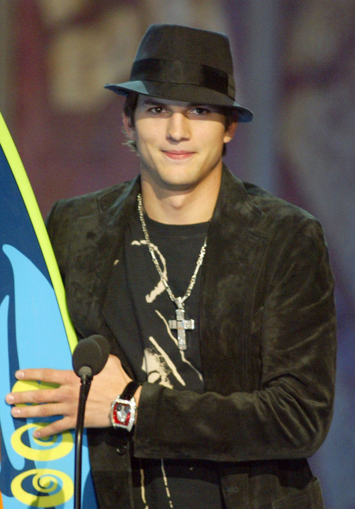 A photo of Ashton Kutcher on stage receiving a Teen Choice surfboard award while wearing a black fedora.