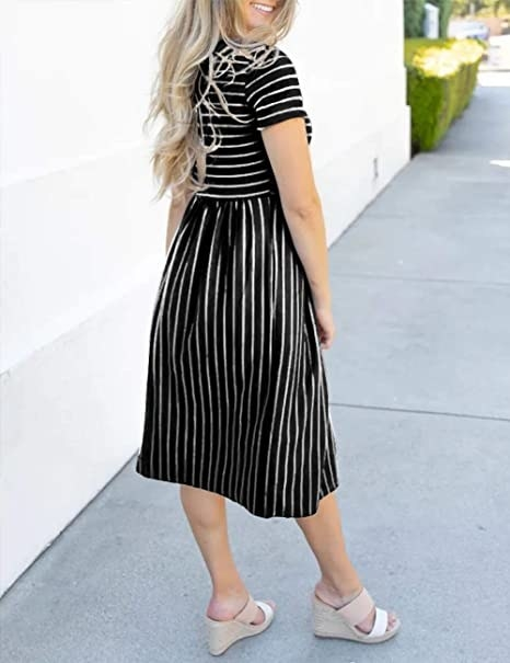 model wearing short sleeve black and white stripe dress with midi length