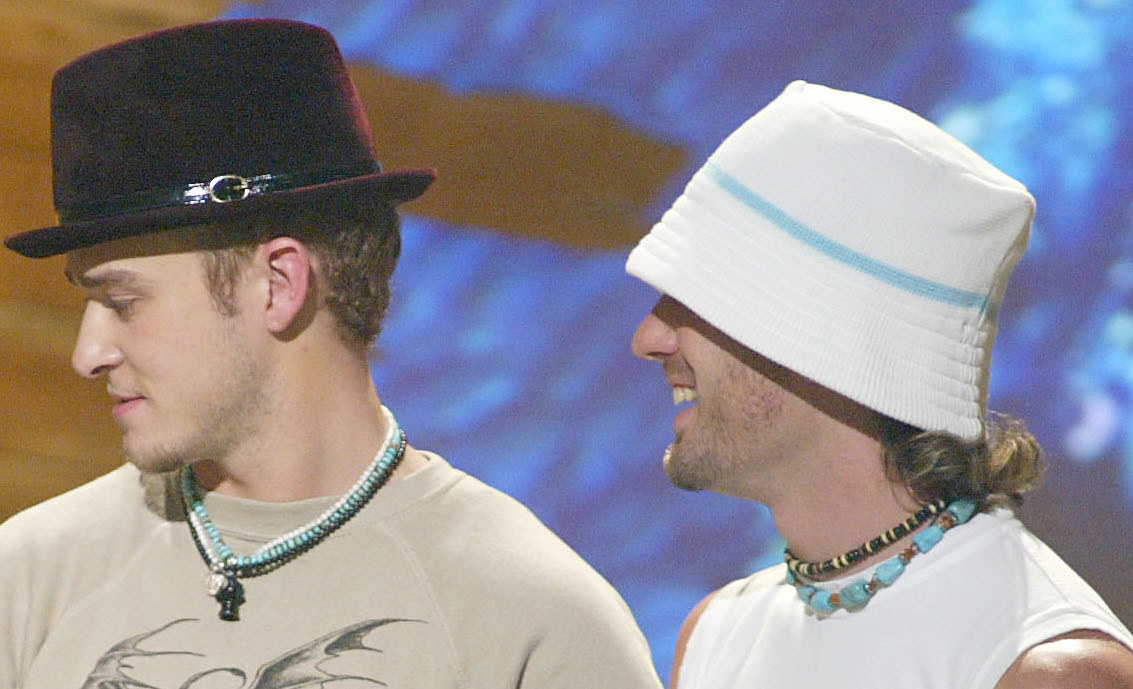 A photo of Justin Timberlake and JC Chasez on stage at each wearing several shell and beaded necklaces.
