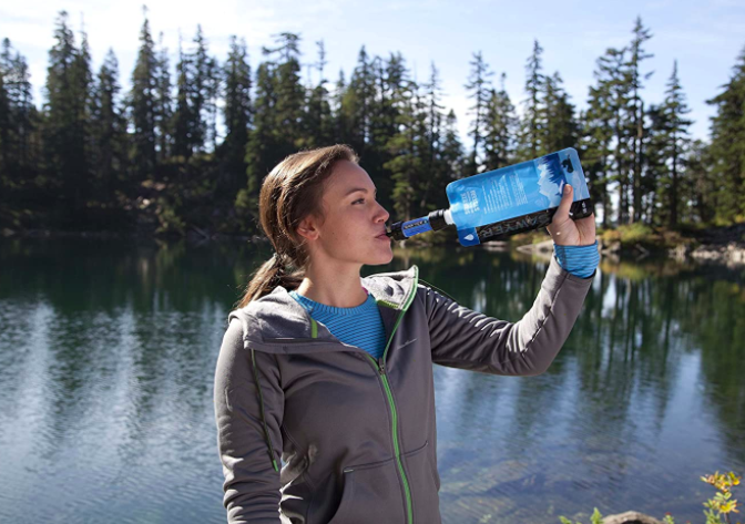Hiker drinks out of personal water filtration system next to a lake