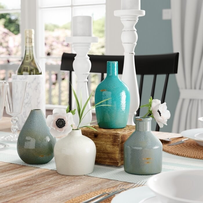 The 4-piece distressed teal and white ceramic vase table set on a dining table
