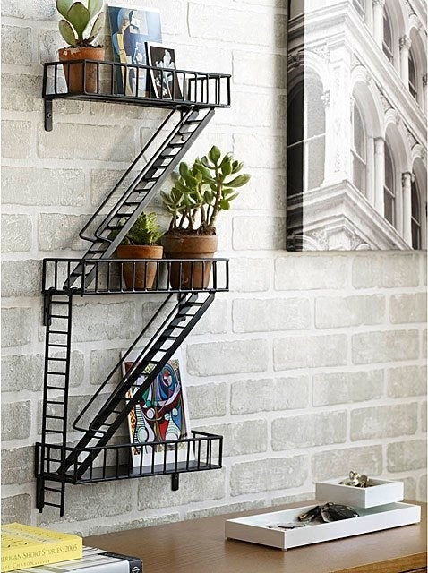 The fire escape shelf hanging above a desk, holding small potted plants and art prints