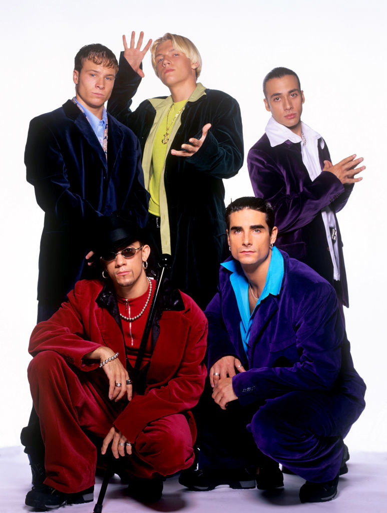 A photo of the Backstreet Boys in velvet suits with Nick Carter making magic hands.